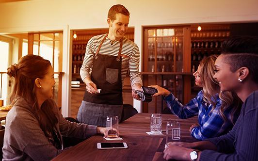 テーブルでクレジットカードによる支払いのための無線デバイスを使用しているウェイター